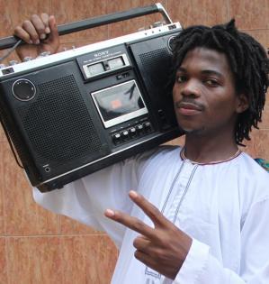 """Hiphopperen Burney Mc med boombox og den arabiske kjorteldragt """"Kanzu"""", som er blevet populær i det ugandiske hiphopmiljø. Både dragt og boombox er del af den nye UNESCO Samling fra Uganda."""