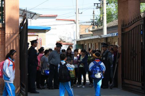 Forældre venter uden for skoleporten i Beijing