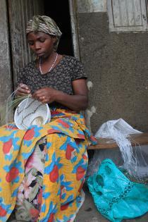 Materialerne bilver genbrugt! - Kvinde i Kisoro syer her en kurv af bananpalme og strimler fra en plastiksæk. Foto Lisbeth Kristine Olesen