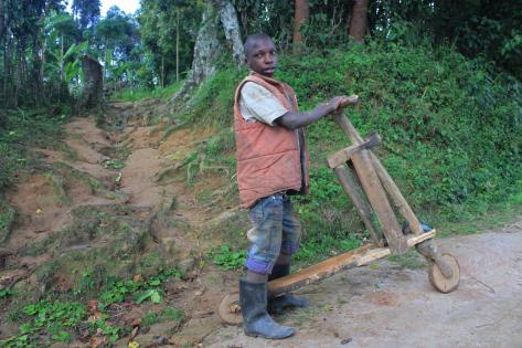 Dreng med hjemmelavet løbehjul i bjergene udenfor Kisoro. Foto af Lisbeth Kristine Olesen